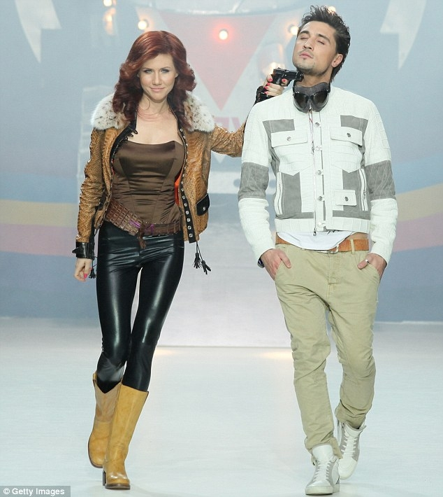 Former Russian spy Anna Chapman works the runway in a designer coat, while managing to hold a fellow model hostage with a pistol to his throat.