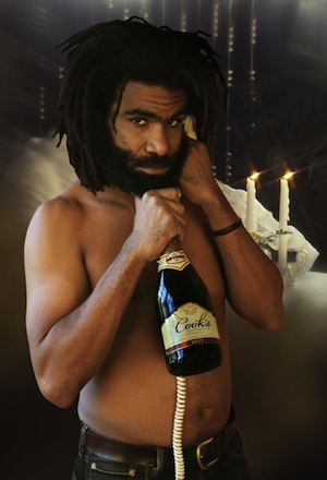 A man posing shirtless with a bottle of champaign.