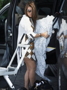 Photo of Kourtney Kardashian carrying baby gear, with Spanx showing.