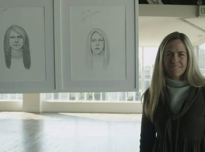 Woman poses with her sketches from the Dove Real Beauty Ad Campaign.