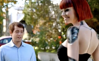 Still from Kia commercial of man seemingly starting at the robotic woman's breasts.