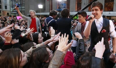 Photograph of British boy band One Direction performing in front of a large audience of young females.