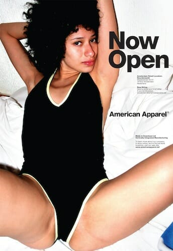 "American Apparel ad with words ""Now Open"" featuring a young woman in a body suit with her legs spread."