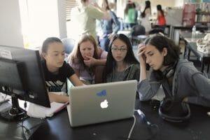 Photo of girls around macbook at camp.