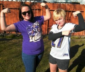 Two young women posing in football attire.