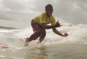 Nasima, posing for a photo while catching a wave.