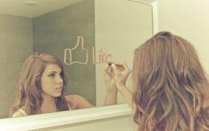 girl writing the word like on mirror
