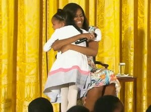 """First Lady Michelle Obama gives an enthusiastic hug to Anaya Brodie for telling Ms. Obama that she looked """"too young for a 51-year-old."""""""